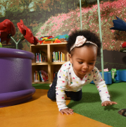 A baby crawling in a Storyville play area