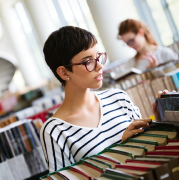 A woman in a striped shirt looking at books.